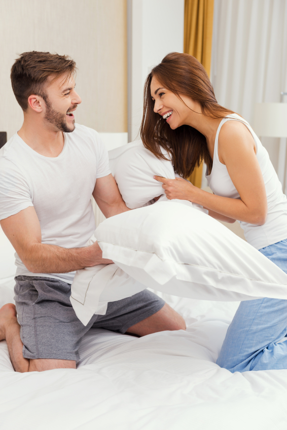 Pillow fight. Beautiful young couple fighting with pillows in bed and smiling